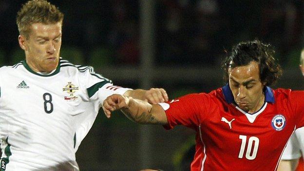 Northern Ireland skipper Steven Davis battles for the ball with Jorge Valdivia of Chile