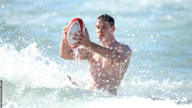 Liam Williams and the Welsh players hold a recovery session in the sea.
