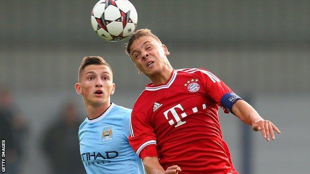 Manchester City's Sinan Bytyqi heads the ball ahead of Bayern Munich's Angelos Oikonomou