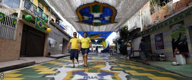 A Brazilian couple walks on a painted and decorated street to celebrate the 2014 World Cup at a residential area in Manaus