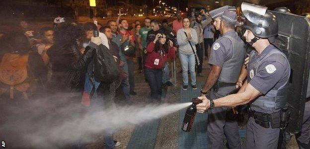 A police officer pepper sprays strikers and protesters during a clash with riot police in front of the Ana Rosa metro station, in an ongoing subway strike by operators in Sao Paulo, Brazil, on 9 June 9, 2014