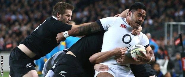Richie McCaw tries to pull Manu Tuilagi back as two of more New Zealanders struggle to bring the England centre to ground