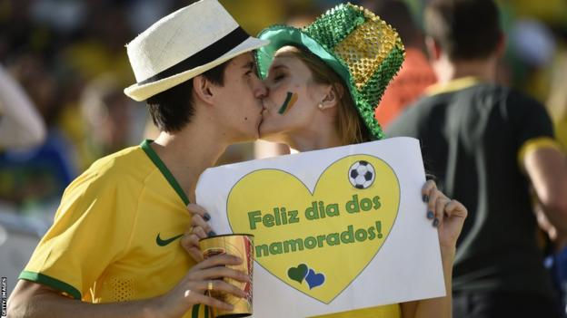 "Brazilian fans embrace and hold a sign that reads ""Happy day of lovers"" before the World Cup opener between Brazil and Croatia at the Arena de Sao Paulo"