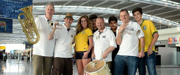 The official England band brought the party spirit to the airport on their way to Brazil