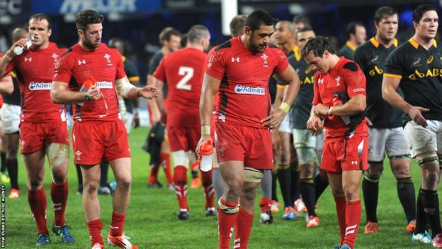 Dejected Wales players leave the pitch following their 38-16 defeat to South Africa in Durban.