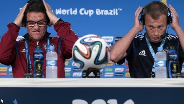 Fabio Capello, Italian coach of Russia, and defender Vasily Berezutsky arrive for a news conference on 16 June