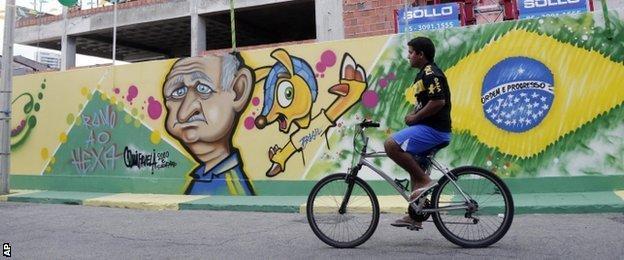 A cyclist passes a Brazil mural in Fortaleza