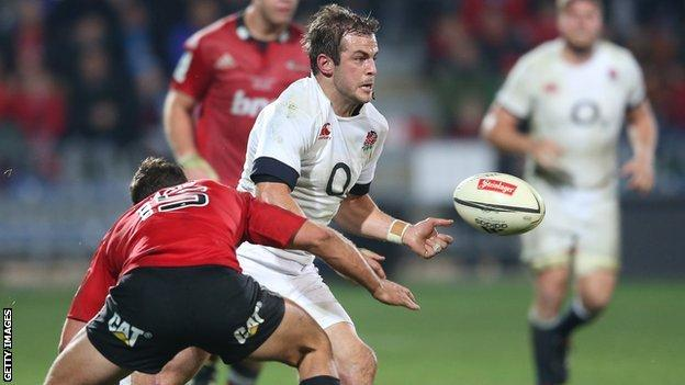 England fly-half Stephen Myler offloads under pressure against the Crusaders