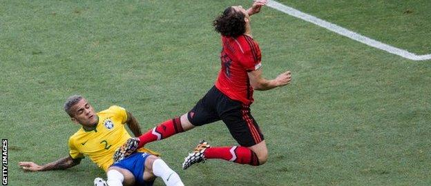 Brazil's Dani Alves challenges Mexico's Andres Guardado.