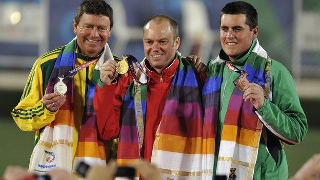 Australia's Leif Selby (C), Wales' Rob Weale (L) and Northern Ireland's Gary Kelly pose with their respective gold, silver and bronze medals during the men's lawn bowls singles awards...