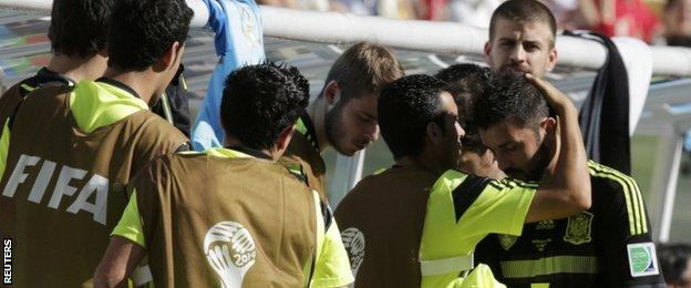 David Villa (far right) is consoled by his team-mates after coming off