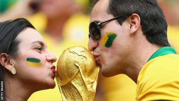 Brazil fans kiss a replica of the World Cup trophy at the Estadio Nacional during the Brazil v Cameroon game