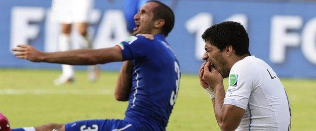Luis Suarez holds his mouth after clashing with Girgio Chiellini