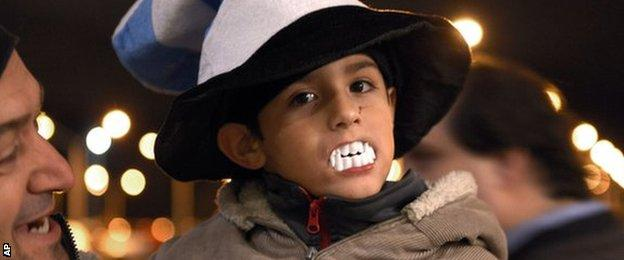 A child shows his support for Suarez by wearing plastic vampire's teeth at Carrasco International Airport near Montevideo