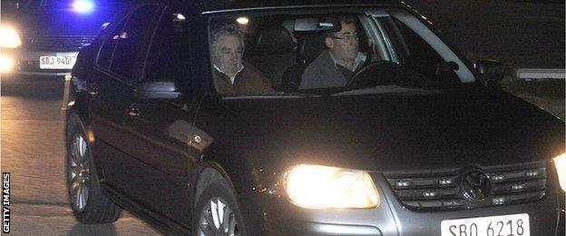 Uruguay's President Jose Mujica (L) leaves in a private car at the Carrasco international airport