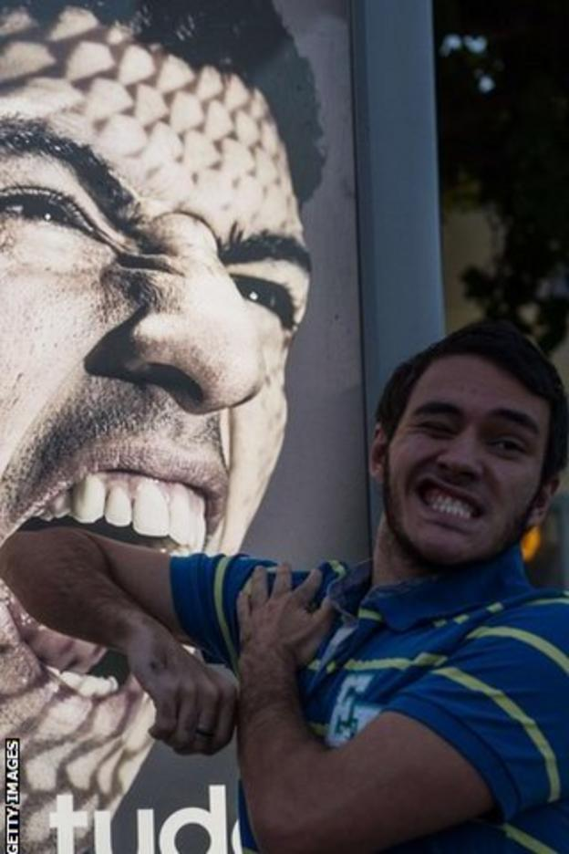 A man holds his arm in front of an advertising placard showing Suarez flashing his teeth at Copacabana beach in Rio de Janeiro
