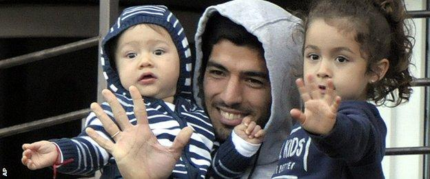 Luis Suarez waves to fans who came to show their support to him following his return to Uruguay