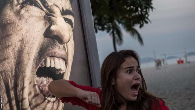 A tourist jokes in front of an advertisement featuring the portrait of Uruguay's forward Luis Suarez at Copacabana beach in Rio de Janeiro