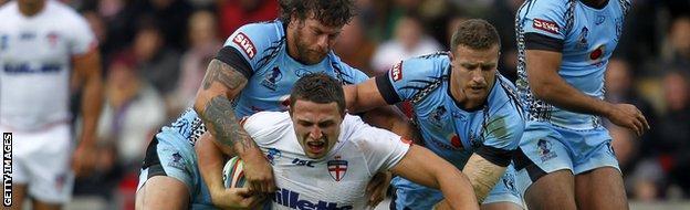 Ashton Sims (l) tackles England's Sam Burgess