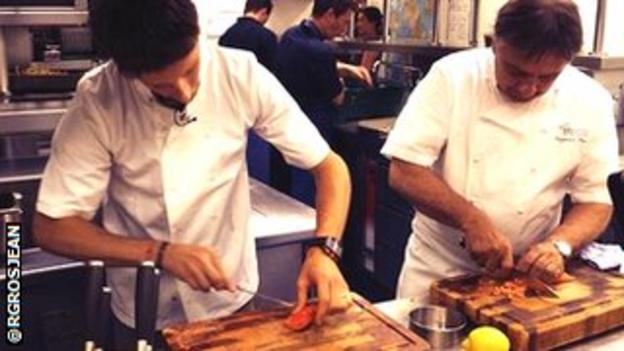 Lotus driver Romain Grosjean is taught some new culinary skills by Raymond Blanc