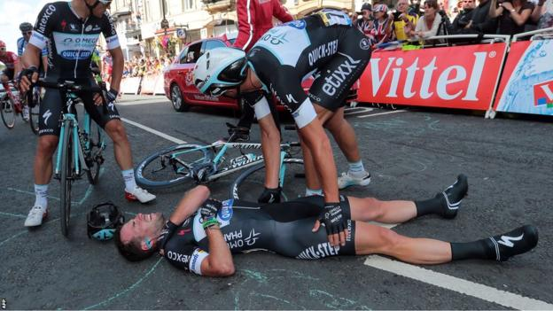 Mark Cavendish lies injured on the ground after crashing heavily during the sprint finish