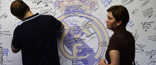 A man writes a message on a wall to pay tribute to Real Madrid's late honorary president Alfredo Di Stefano