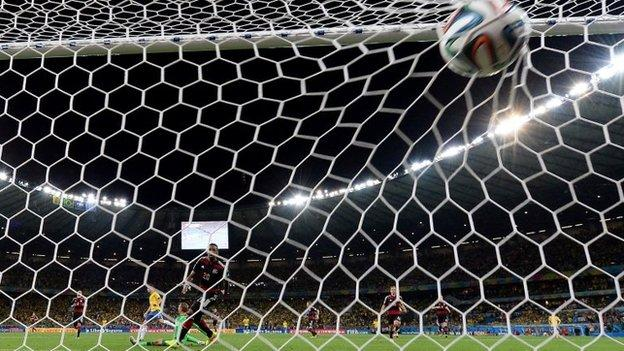 """Brazil""""s midfielder Oscar (L) scores against Germany""""s goalkeeper Manuel Neuer during the semi-final football match between Brazil and Germany at The Mineirao Stadium in Belo Horizonte"""