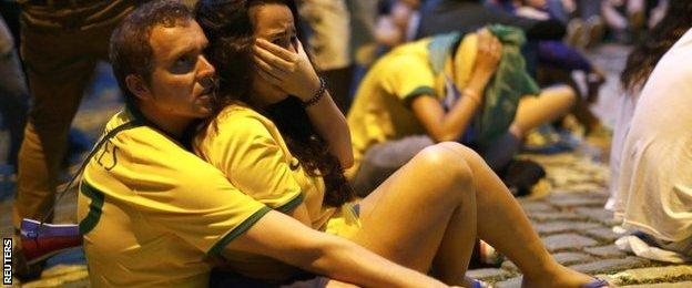 Brazil fans react as they watch their 2014 World Cup semi-finals against Germany on a street in Rio de Janeiro
