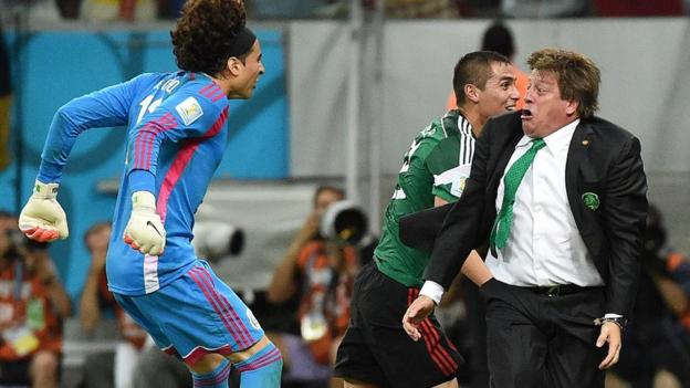Mexico's goalkeeper Guillermo Ochoa (L) and Mexico's coach Miguel Herrera (R) celebrate a goal by their team during a Group A football match between Croatia and Mexico at the Pernambuco Arena in Recife