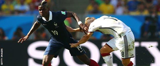 Paul Pogba is challenged by Germany's Toni Kroos