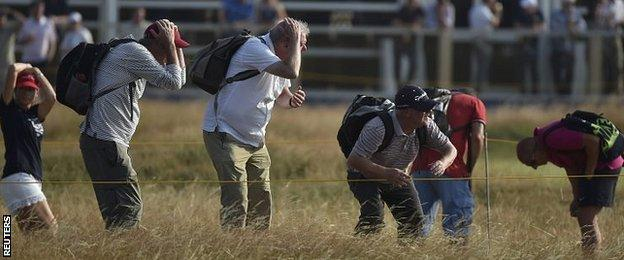 Spectators take cover to avoid a wayward tee shot from Tiger Woods