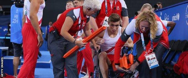 Sam Oldham in a wheelchair after falling in the vault