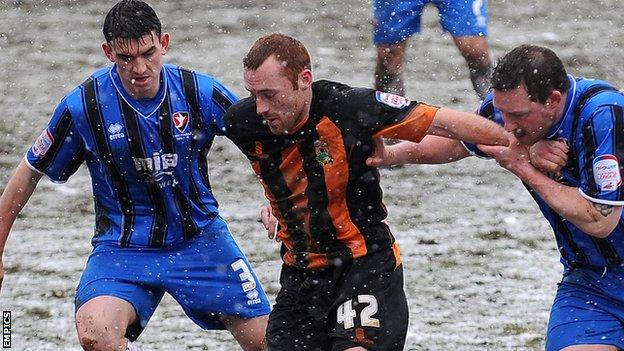 Harry Crawford (centre) battles with Cheltenham's Billy Jones (left) and Steve Elliott (right).