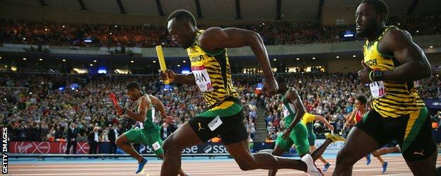 Usain Bolt takes the baton in the 4x100m relay heat at the Commonwealth Games