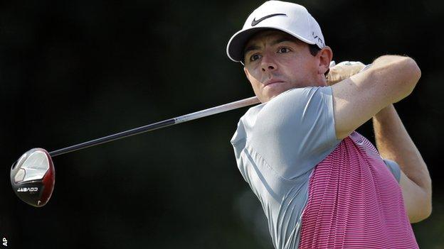 McIlroy watches his tee shot at the 14th in Friday's second round