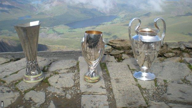 The Uefa Champions League, Europa League and Super Cup trophies were taken to the top of Snowdon to mark the staging of the Super Cup final in Cardiff on 12 August