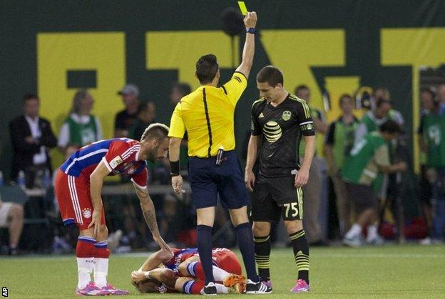 Will Johnson is booked for fouling and injuring Bastian Schweinsteiger