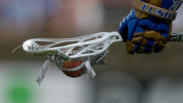 hand carrying a lacrosse racket and ball