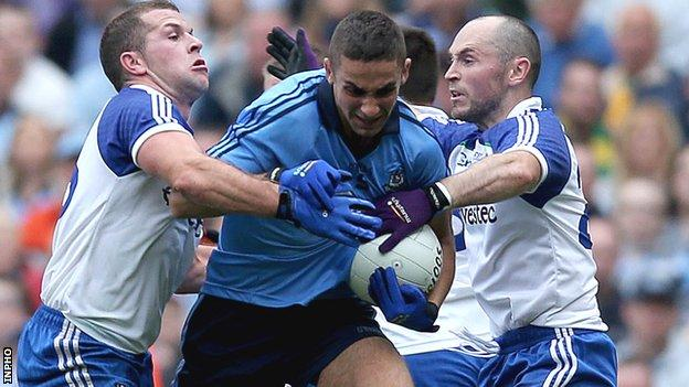 Two Monaghan players tackle Dublin's James McCarthy
