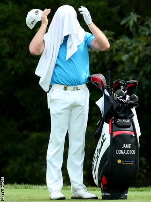 Jamie Donaldson cools off under a wet towel in the US PGA at Valhalla as he completes the third round in 66