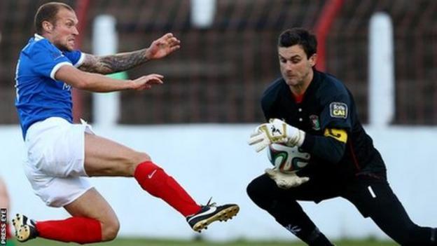 Linfield player-manager Warren Feeney stretches as Glentoran goalkeeper Elliott Morris gathers the ball