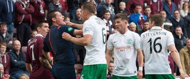 Hibs defender Jordon Forster is held by assistant referee Gavin Harris during a heated exchange with Jamie Walker of Hearts