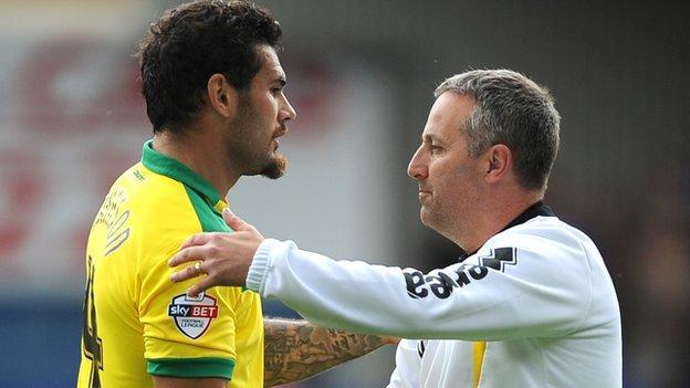 Neil Adams celebrates with Bradley Johnson after Norwich's 1-0 win over Ipswich.