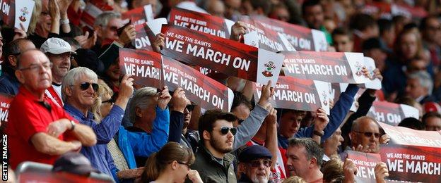 Saints fans hold up signs during the Barclays Premier League match between Southampton and West Bromwich Albion