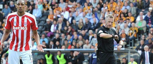 Referee Jonathan Moss checks the goal line technology on his watch before awarding a goal to Stoke City's Ryan Shawcross