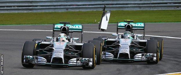 Rosberg (right) clips the back of Hamilton's car