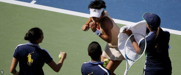 Three ballkids try to help Kimiko Date-Krumm when she is attacked by a bee