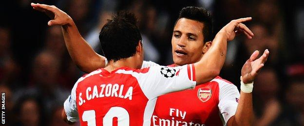 Alexis Sanchez celebrates with team mate Santi Cazorla of Arsenal after scoring during the UEFA Champions League Qualifier 2nd leg match between Arsenal and Besiktas