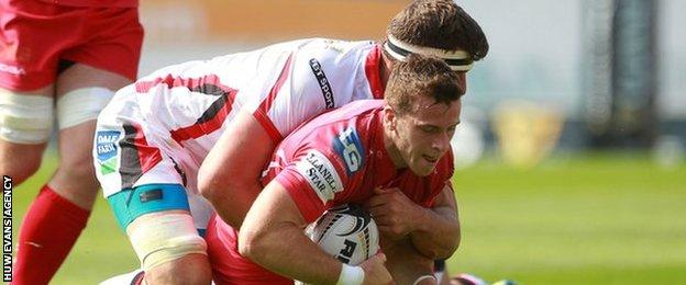 Gareth Davies of Scarlets is tackled by Robbie Diack and Callum Black of Ulster