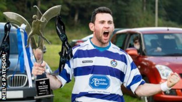 A Newtonmore player celebrates with the Premiership trophy